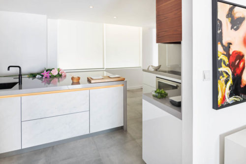 Broccoli in White kitchen with grey countertop and wood wall cabinets in Dubai by Goettling Interiors.