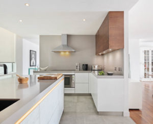 Grip ledge lighting in White kitchen with grey countertop and wood wall cabinets in Dubai by Goettling Interiors.