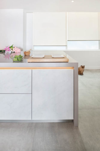 Lilies & broccoli in White kitchen with grey countertop and wood wall cabinets in Dubai by Goettling Interiors.