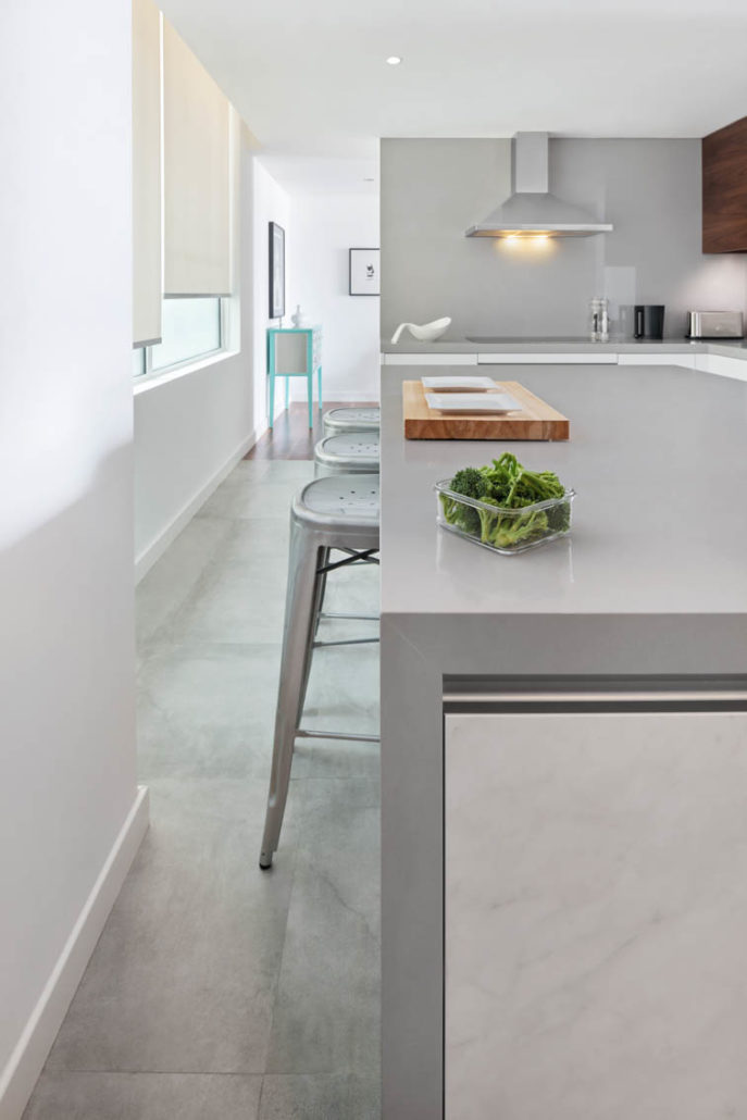 Industrial Metal bar stools in White kitchen with grey countertop and wood wall cabinets in Dubai by Goettling Interiors.