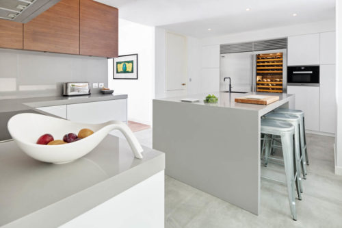 Fruits in White kitchen with grey countertop and wood wall cabinets in Dubai by Goettling Interiors.