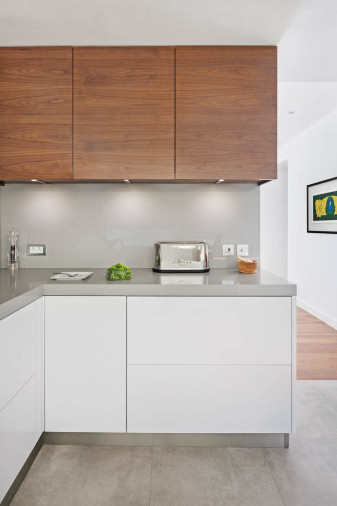 Toaster and broccoli in White kitchen with grey countertop and wood wall cabinets in Dubai by Goettling Interiors.