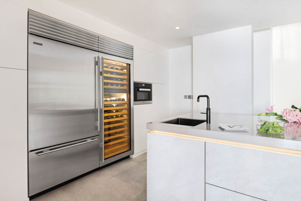 Fridge and wine fridge in White kitchen with grey countertop and wood wall cabinets in Dubai by Goettling Interiors.